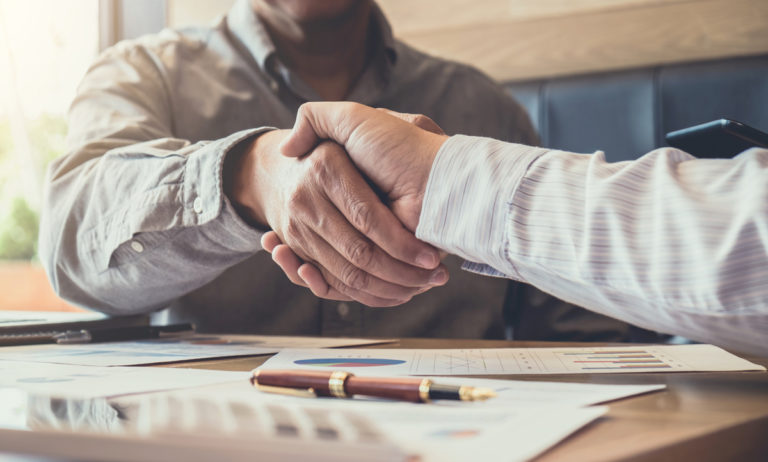 Employee from a bank-owned insurance agency shaking hands with a client